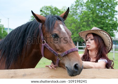 Beautiful brunette girl speaks with a horse
