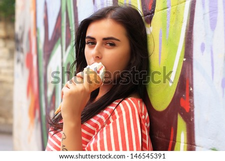 Beautiful brunette girl stands near the wall with graffiti on a warm sunny day. fashion portrait