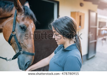 Beautiful brunette girl taking care of her horse. Selective focus on girl's face.