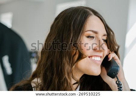 beautiful brunette girl talking on home phone - stock photo