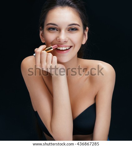 Beautiful brunette girl toothy smiling with lipstick. Close up of an attractive girl of European appearance on black background. - stock photo