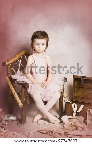 Beautiful brunette girl wearing a ballet costume on pink background