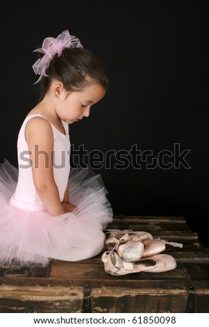 Beautiful brunette girl wearing a pink tutu sitting by pointe shoes - stock photo