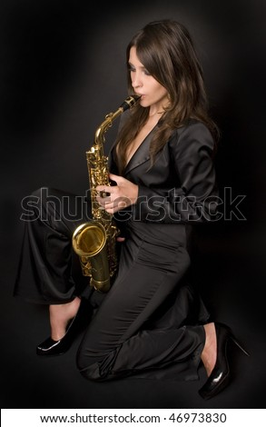 beautiful brunette girl wearing black suit is playing her saxophone against the black background