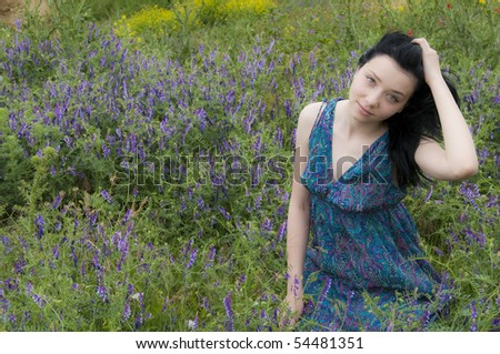 Beautiful Brunette Girl  with  Blue Dress in Blue Flowers - stock photo