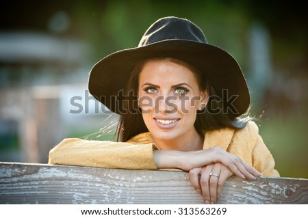Beautiful brunette girl with country look near an old wooden fence. Attractive woman with black hat and yellow coat,  American country style farmer. Long hair dark hair female in rustic style - stock photo
