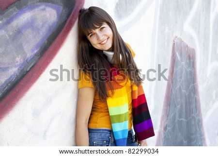 Beautiful brunette girl with headphones and graffiti wall - stock photo