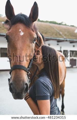 Beautiful brunette girl with her horse. Selective focus on girl.