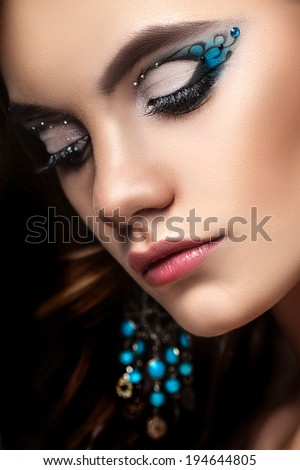 beautiful brunette girl with long curly hair and creative makeup - stock photo