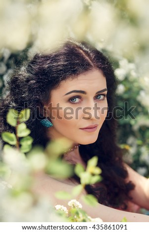 Beautiful brunette girl with long curly hair in a beautiful pink dress sitting in the park among the blooming Spirea, closeup portrait, headshot.