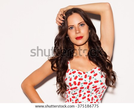 Beautiful brunette girl with long hair and blue eyes posing in bright summer short dress nex to white background. Close up. Indoor - stock photo