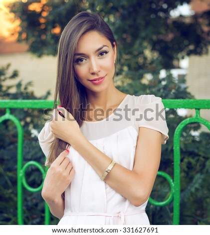 Beautiful brunette girl with long hair outdoors, summer in the city, bright lipstick pink dress, tanned skin. Happy business woman relaxing. Fashion lifestyle, urban style. - stock photo