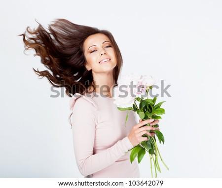 Beautiful brunette girl with peony flower in studio - stock photo