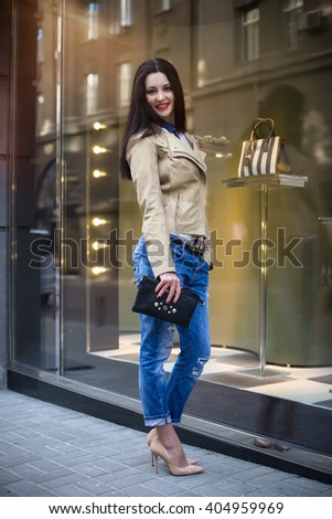 Beautiful brunette girl with perfect make-up, red lips, wearing a beige coat, white shirt, posing  in just bought things near glass wall of the shopping center.  - stock photo