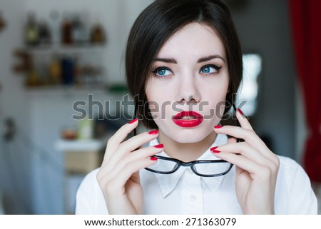 beautiful brunette girl with red lips takes off her glasses and posing in the apartment - stock photo