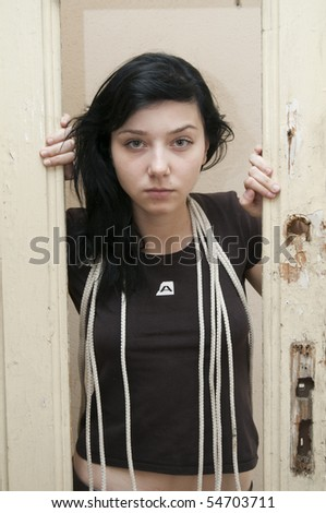 Beautiful Brunette girl with rops and old door - stock photo