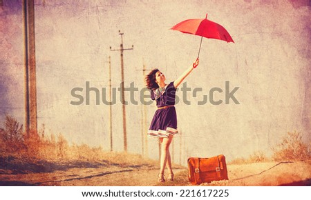 Beautiful brunette girl with suitcase and umbrella on the countryside road.