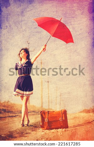 Beautiful brunette girl with suitcase and umbrella on the countryside road. - stock photo