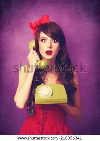 Beautiful brunette girl with telephone on violet background. - stock photo