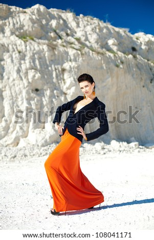 Beautiful brunette girl with trendy makeup and fashionable clothes posing in a rock. Summer. Black and white photo