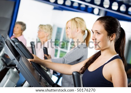 Beautiful brunette girl working out at the gym with a group of friends - stock photo