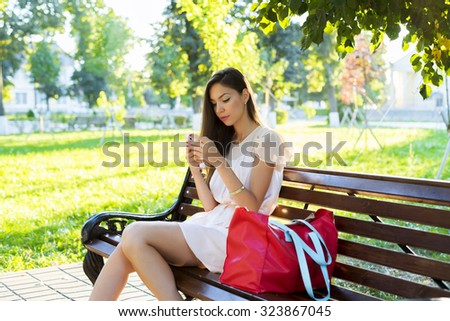 Beautiful brunette girl writing a message phone park sitting on a bench in a dress, summer day business woman, relaxing after work, fashion style, city life in social networks reads the news feed - stock photo