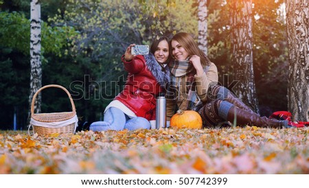 Beautiful brunette girls making selfie on a picnic in autumn park sitting  the fallen leaves near the pumpkin at halloween time.