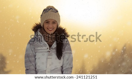 Beautiful brunette hair girl enjoying the snow at sunset in winter season. - stock photo