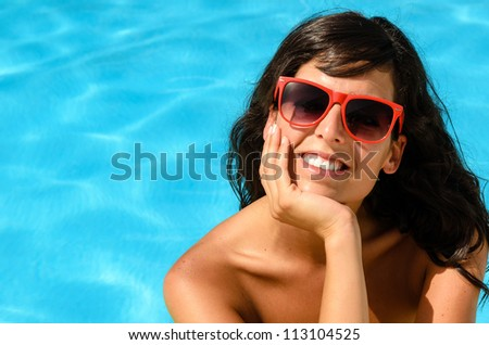Beautiful brunette happy face looking cheerful at camera in a pool on blue water background. Summer hot day in pool with caucasian smiling model. - stock photo