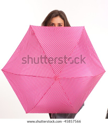 Beautiful brunette hiding behind a bright umbrella - stock photo