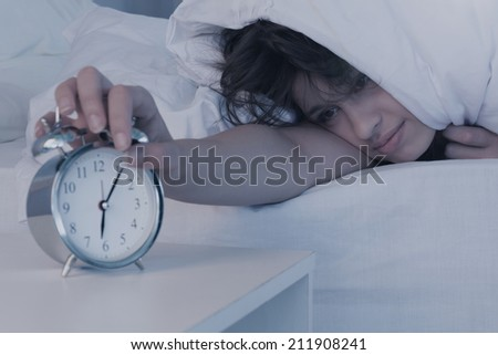 Beautiful brunette hitting alarm clock from under duvet at home in the bedroom - stock photo
