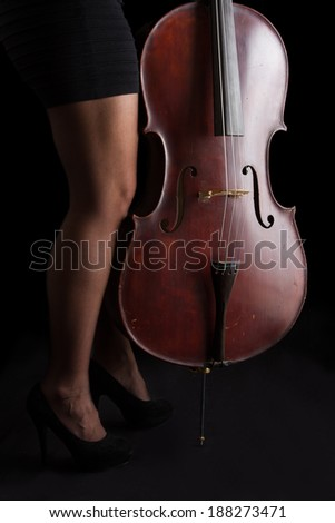 Beautiful brunette holding a cello with selective light in black dress