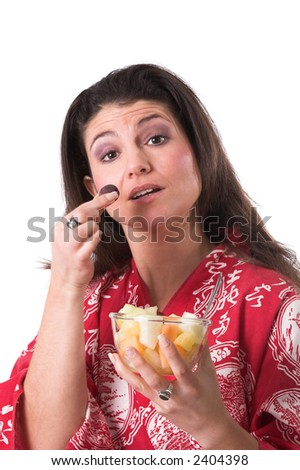 Beautiful brunette holding a healthy grape in her hands and a bowl of fruit - stock photo