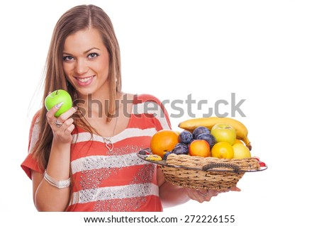 Beautiful brunette holding a punnet full of fresh fruit - stock photo