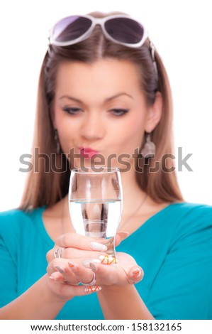 Beautiful brunette holding half full glass of water, isolated on white - stock photo