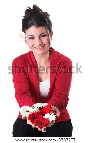 beautiful brunette holding out a hand filled with daisies - stock photo