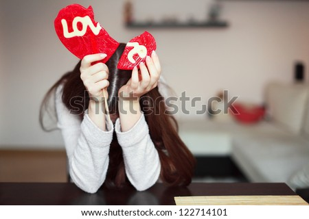 Beautiful brunette holding two parts of broken heart - stock photo