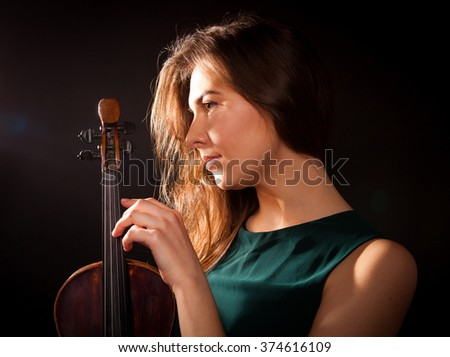 beautiful brunette holds a violin in his hands, photo on black background in the studio