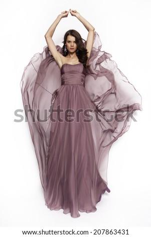 Beautiful brunette in a cocktail,long dress posing in studio - stock photo