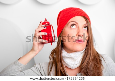 beautiful brunette in a red hat listening alarm clock  - stock photo