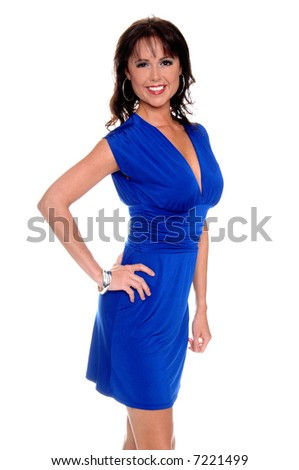 Beautiful brunette in a sleek blue cocktail dress with a big smile and her hand on her hip - stock photo