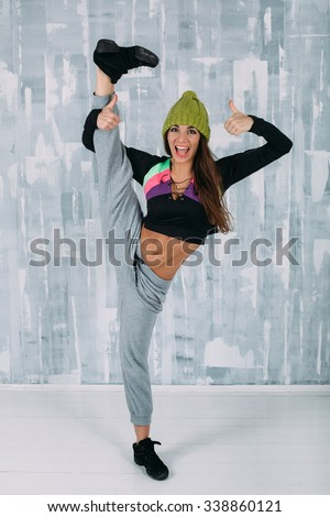 Beautiful brunette in funny knitted green hat and casual clothes stay in gymnastic pose, smile and show thumbs up. Slim gymnast posing. Balance posing  - stock photo