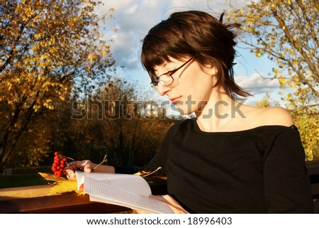 beautiful brunette in glasses reading book in autumn park - stock photo