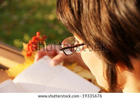 beautiful brunette in glasses reading book in autumn park, focus on glasses and eyelashes - stock photo