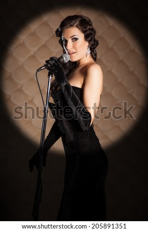 Beautiful brunette in retro style clothes with a microphone sings a song on stage - stock photo