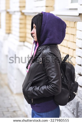 Beautiful brunette in the hood in the autumn, on the street. Fashion lifestyle. Close-up on a cloudy day, a young girl in the street. - stock photo