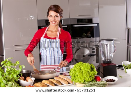 Beautiful brunette in the kitchen baking an egg and smiling - stock photo