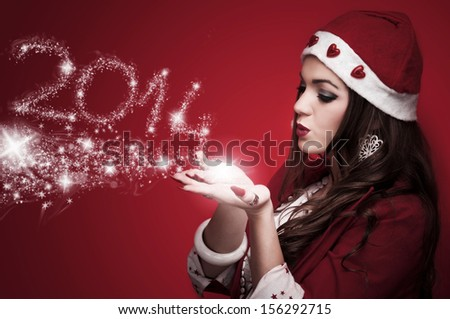 Beautiful brunette in the Santa costume blowing snowflakes and make New Year numbers 2014 - stock photo
