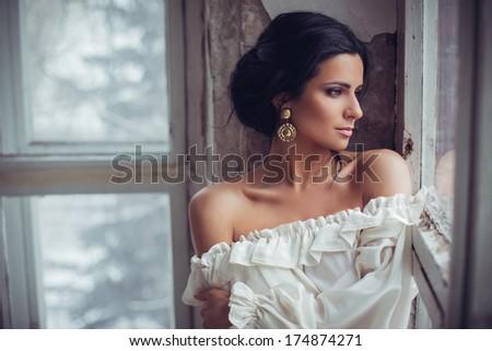 Beautiful brunette in white dress posing indoors - stock photo