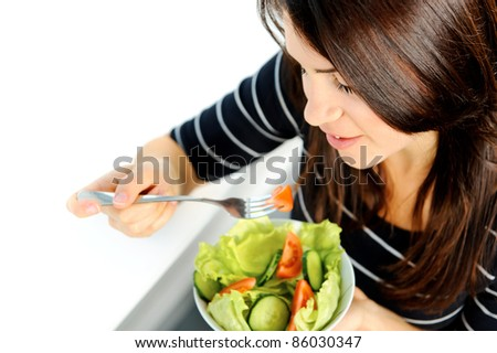 Beautiful brunette is eating a healthy green salad - stock photo